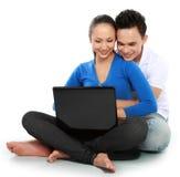 Pares con la computadora portátil, sentándose en suelo Foto de archivo libre de regalías