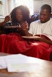 Pares con la dieta de los pobres que se sienta en Sofa Eating Meal Fotos de archivo libres de regalías
