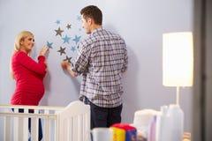 Pares con la esposa embarazada que añade decoraciones al cuarto de niños foto de archivo