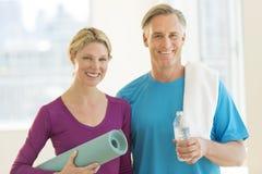 Pares con la estera del ejercicio; Botella de agua y toalla en club Imagen de archivo libre de regalías