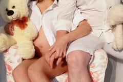 Pares con la mujer embarazada que se relaja en chairTogether fotografía de archivo libre de regalías