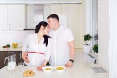 Pares con la mujer embarazada que se relaja en cocina junto Fotografía de archivo