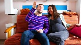 Pares con la mujer embarazada que se relaja en el sofá