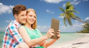 Pares con la PC de la tableta que toma el selfie sobre la playa Foto de archivo
