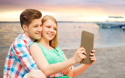 Pares con la PC de la tableta que toma el selfie sobre la playa Fotos de archivo