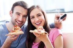 Pares con la pizza y el telecontrol de la TV Fotografía de archivo libre de regalías