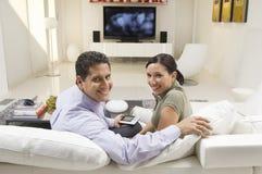 Pares con la sentada teledirigida en el sofá foto de archivo libre de regalías