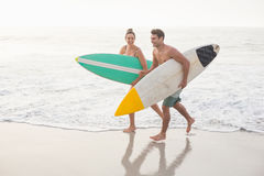 Pares con la tabla hawaiana que corre en la playa Imagenes de archivo