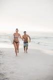 Pares con la tabla hawaiana que corre en la playa Foto de archivo
