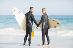 Pares con la tabla hawaiana que lleva a cabo la mano en la playa Imágenes de archivo libres de regalías