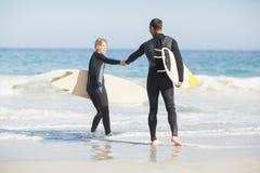 Pares con la tabla hawaiana que lleva a cabo la mano en la playa Fotografía de archivo