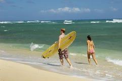 Pares con la tabla hawaiana que recorre en la playa Imágenes de archivo libres de regalías