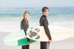 Pares con la tabla hawaiana que se coloca en la playa Imagen de archivo