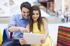 Pares con la tableta en alameda de compras Imágenes de archivo libres de regalías