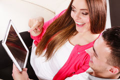 Pares con la tableta que se sienta en el sofá en casa Fotos de archivo libres de regalías