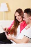 Pares con la tableta que se sienta en el sofá en casa Imágenes de archivo libres de regalías
