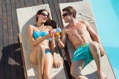 Pares con las bebidas en ociosos del sol por la piscina Imágenes de archivo libres de regalías