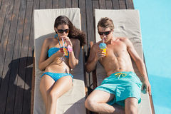 Pares con las bebidas en ociosos del sol por la piscina Imagenes de archivo