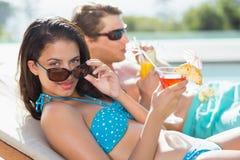 Pares con las bebidas por la piscina Fotos de archivo libres de regalías