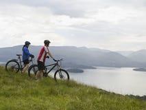 Pares con las bicicletas por el lago Imágenes de archivo libres de regalías