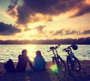 Pares con las bicicletas que se relajan en la puesta del sol fotos de archivo libres de regalías
