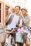 Pares con las bicicletas y smartphone en la ciudad Imágenes de archivo libres de regalías