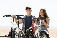 Pares con las bicis en la playa foto de archivo