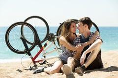 Pares con las bicis en la playa fotografía de archivo