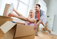 Pares con las cajas de cartón que se divierten en el nuevo hogar Foto de archivo libre de regalías