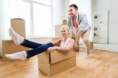 Pares con las cajas de cartón que se divierten en el nuevo hogar Imágenes de archivo libres de regalías