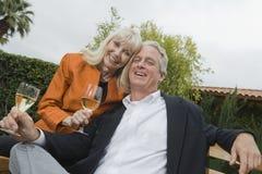 Pares con las copas de vino en jardín Imagen de archivo libre de regalías