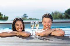 Pares con las flautas de champán en piscina Foto de archivo libre de regalías