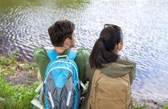 Pares con las mochilas que se sientan en la orilla del río Imagen de archivo