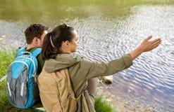 Pares con las mochilas que se sientan en la orilla del río Imágenes de archivo libres de regalías