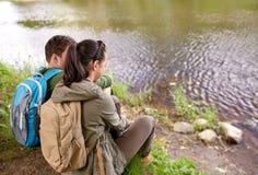 Pares con las mochilas que se sientan en la orilla del río Imagen de archivo libre de regalías