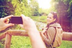 Pares con las mochilas que toman la imagen por smartphone Foto de archivo libre de regalías