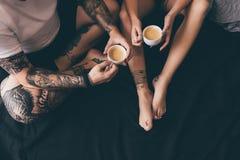 Pares con las tazas de café en cama Fotografía de archivo libre de regalías