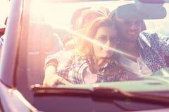 Pares con los amigos que conducen en la puesta del sol Fotos de archivo libres de regalías