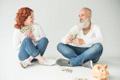 Pares con los dólares y la hucha Imagen de archivo