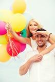 Pares con los globos coloridos en la playa Imagenes de archivo