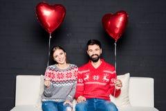 Pares con los globos rojos de los corazones Foto de archivo libre de regalías