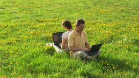 Pares con los ordenadores portátiles en un prado almacen de metraje de vídeo