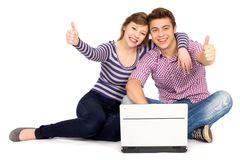 Pares con los pulgares para arriba usando la computadora portátil Imagen de archivo