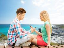 Pares con los smartphones que se sientan en banco Imagen de archivo libre de regalías