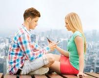 Pares con los smartphones que se sientan en banco sobre ciudad Imagen de archivo