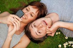 Pares con los teléfonos móviles al aire libre Fotografía de archivo libre de regalías
