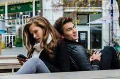 Pares con los teléfonos móviles que se sientan en banco Fotografía de archivo