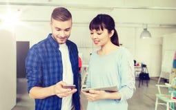 Pares con PC del smartphone y de la tableta en la oficina Fotografía de archivo