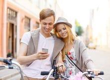 Pares con smartphone y bicicletas en la ciudad Imagen de archivo