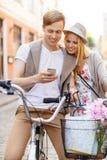 Pares con smartphone y bicicletas en la ciudad Imagenes de archivo